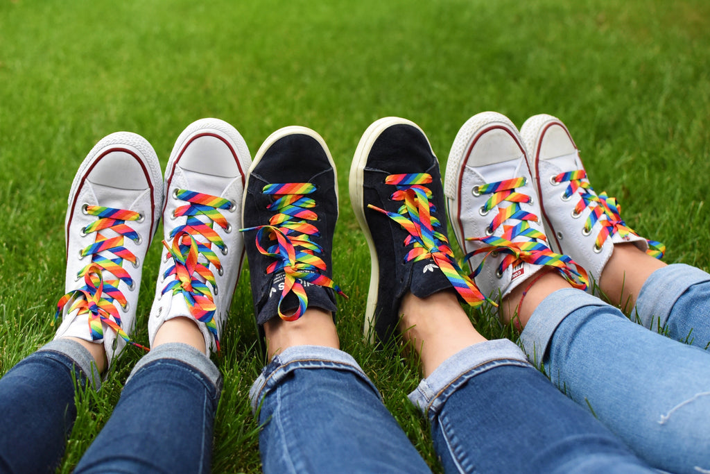 3 women sitting on grass with their feet together wearing matching rainbow striped shoelaces on their sneakers