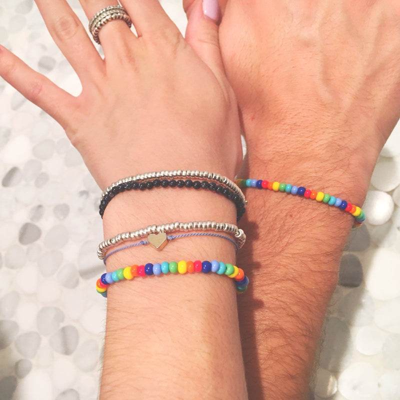 a man and woman's wrist wearing a stack of different bracelets including a rainbow coloured bead bracelet