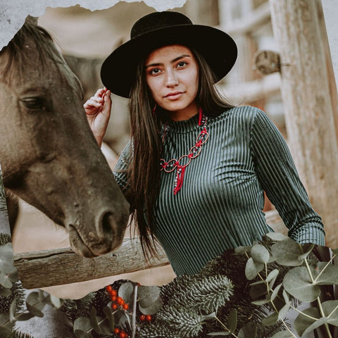 Model wearing Buckaroo Bling necklace and earrings next to a horse; photo superimposed on a background of Christmas tree branches and holly