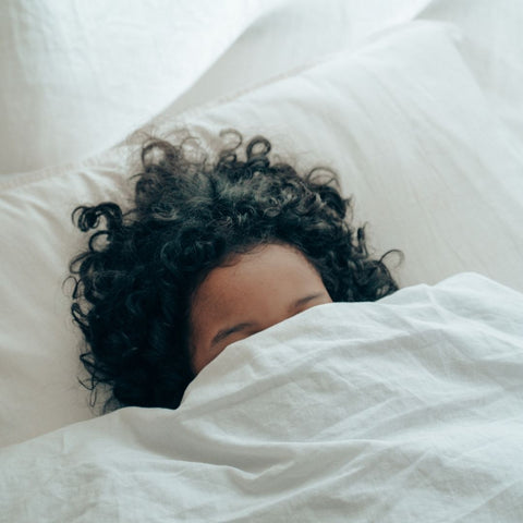 Woman sleeping in bed with her face covered