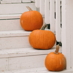 Three orange pumpkins on the stairs - photo by Carson Asher