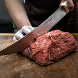 Chef cutting a piece of meat with a big knife