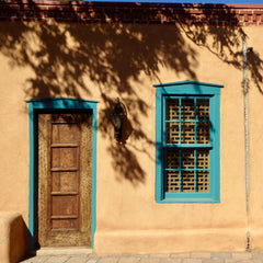 Adobe house with turquoise window and door frames - photo by Matt Briney