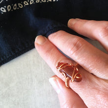 Load image into Gallery viewer, Pure copper wirewrapped ring with large oval carnelian cabochon on a model's hand