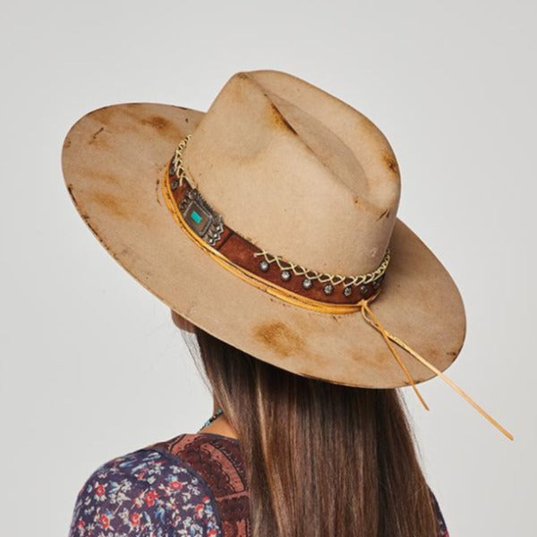 distressed beige rancher hat from Stampede brand. Embellished leather band had silver studs and concho with accenet threading.