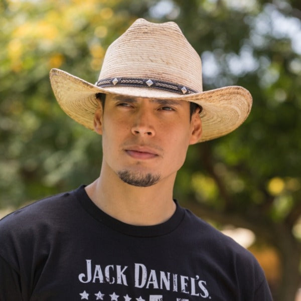 Young man with a black t-shirt and facial hair wearing a palm leaf cowboy hat