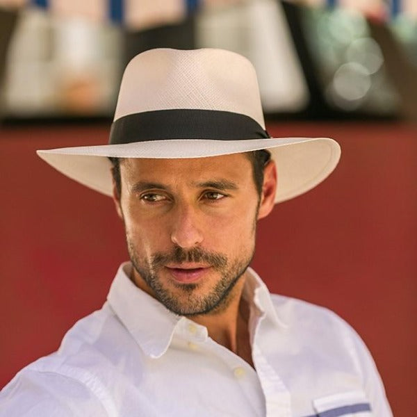 Man wearing white panama straw hat with black band