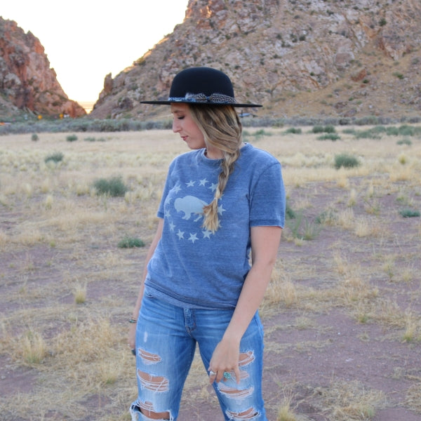 girl in blue jeans with a blue t-shirt wearing on open crown black felt hat
