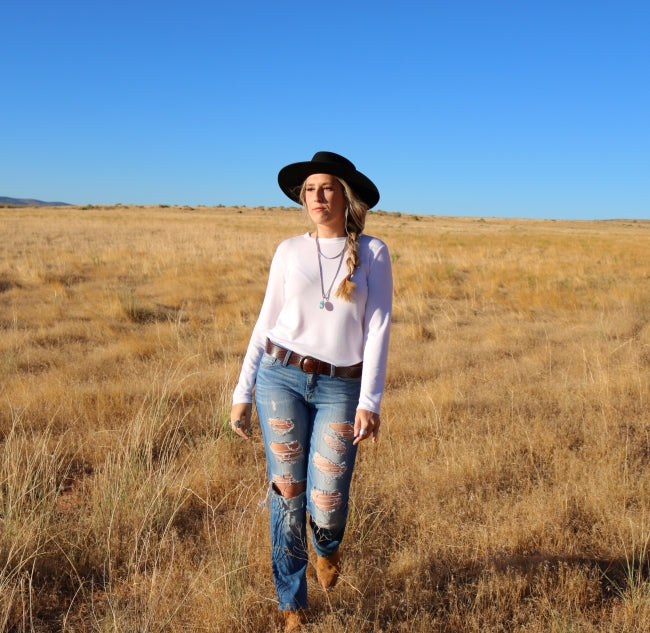 Girl walking through a gold field wearing blue jeans and a black wool rancher hat