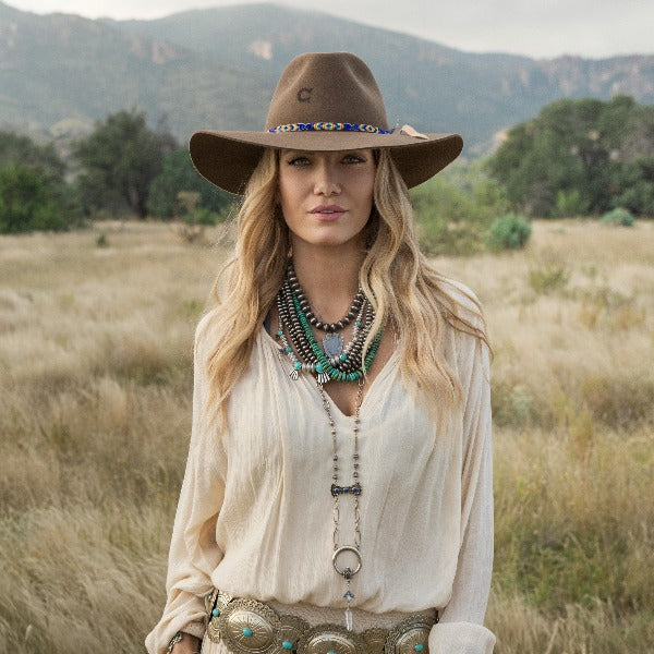 Blonde woman in field wearing brown Charlie 1 Horse cowboy hat with blue and orange band.