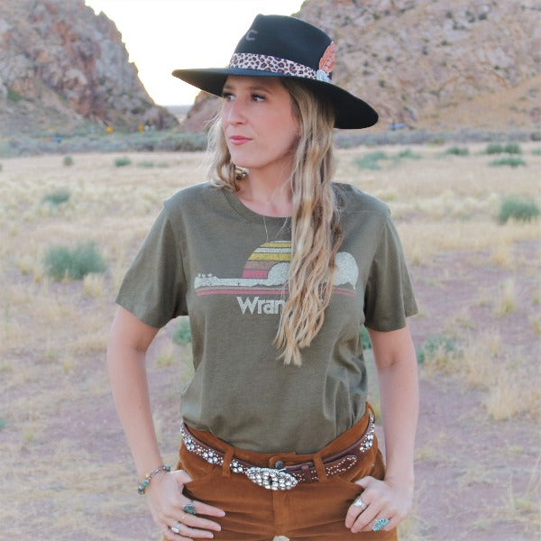 Girl wearing western clothes, and Charlie 1 Horse Black Heatseeker Hat standing behind a desert landscape