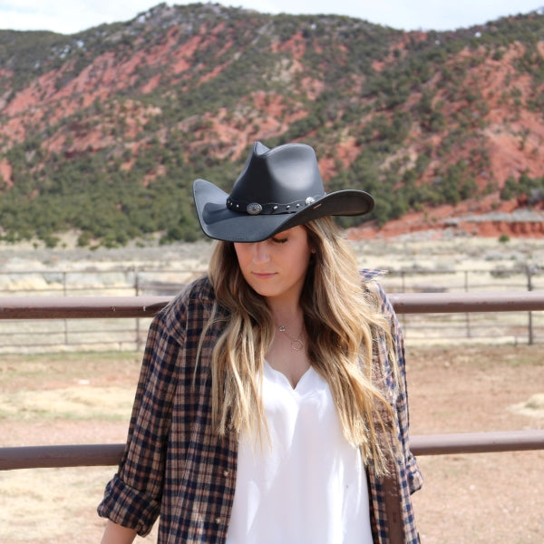 Young woman with long blond hair standing in front of a horse pen iron fence. She is looking down, and wearing a plaid shirt with a black leather stetson cowboy hat.