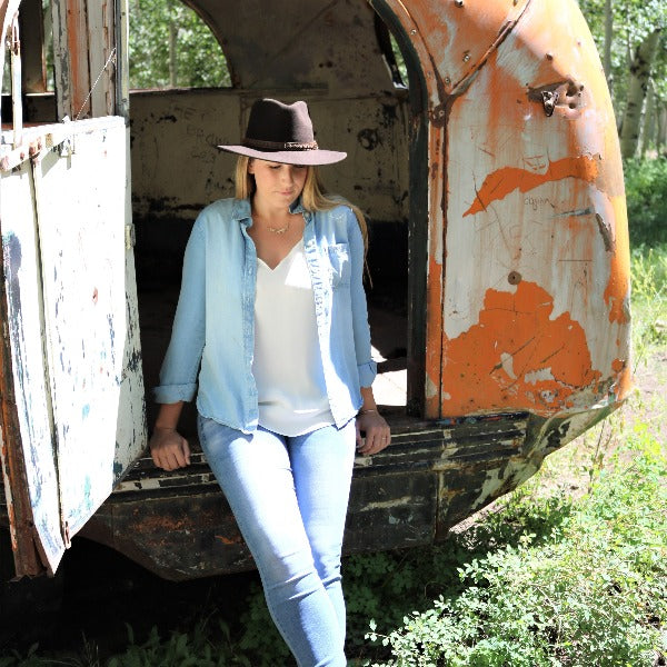 women dressed in a demin shirt and jeans leaning on a beat up vintage yellow school bus wearing a brown felt stampede cowboy hat and cowboy boots