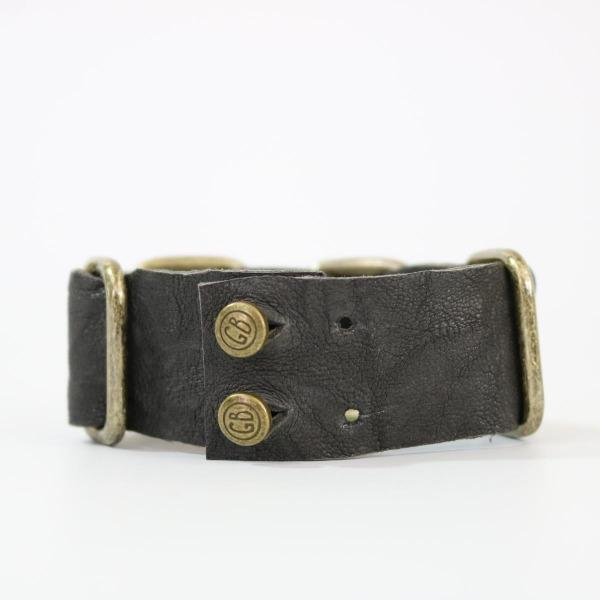 The backside of a men's Grey lamb leather bracelet with brass hardware laying on its side on a white back ground
