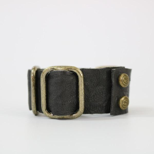 The side view of Grey lamb leather bracelet with brass hardware laying on its side on a white back ground