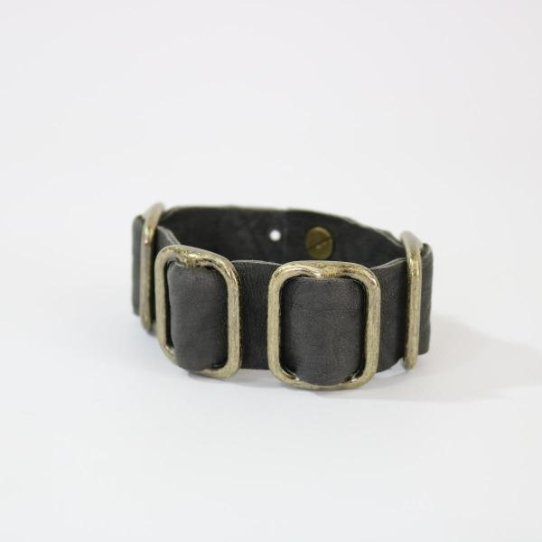 Men's Grey lamb leather bracelet with brass hardware laying on its side on a white back ground