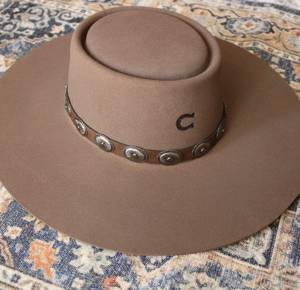 Charlie 1 Horse brown wool gambler hat with conchos on the leather band sitting on top of a colorful vintage rug