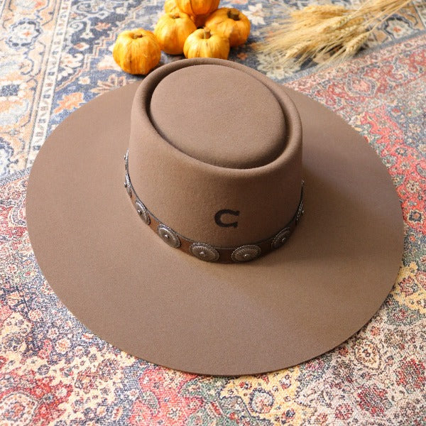 Charlie 1 Horse brown wool gambler hat with conchos on the band. Hat is sitting on a colorful vintage rug with baby pumpkins in the back ground.