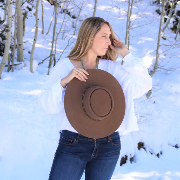 Blonde Woman holding Charlie 1 Horse High Desert Hat in Pecan Color
