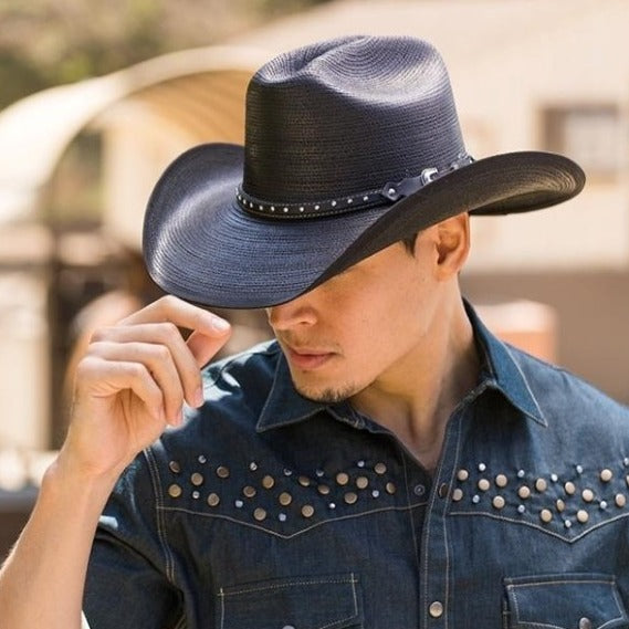 Man wearing black western stampede hat with black band with circle studs