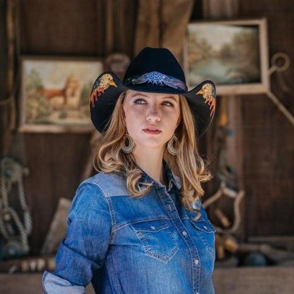 Woman wearing black wool cowboy hat with american eagle decoration