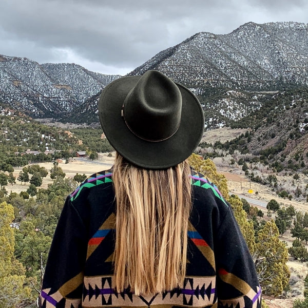 Girl with long blonde hair looking at the utah mountains. she is wearing an aztec print jacket and sage colored stetson hat. The mountians are in the distance and lightly snow covered.