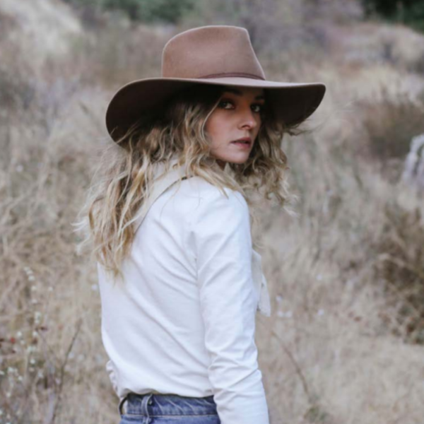 Woman with curly hair wearing brown stetson wool rancher hat