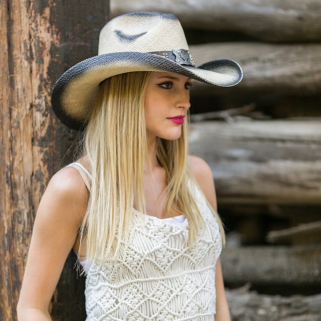 blonde women wearing white tank top and black stained straw panama women's western stampede hat in front of wood cabin