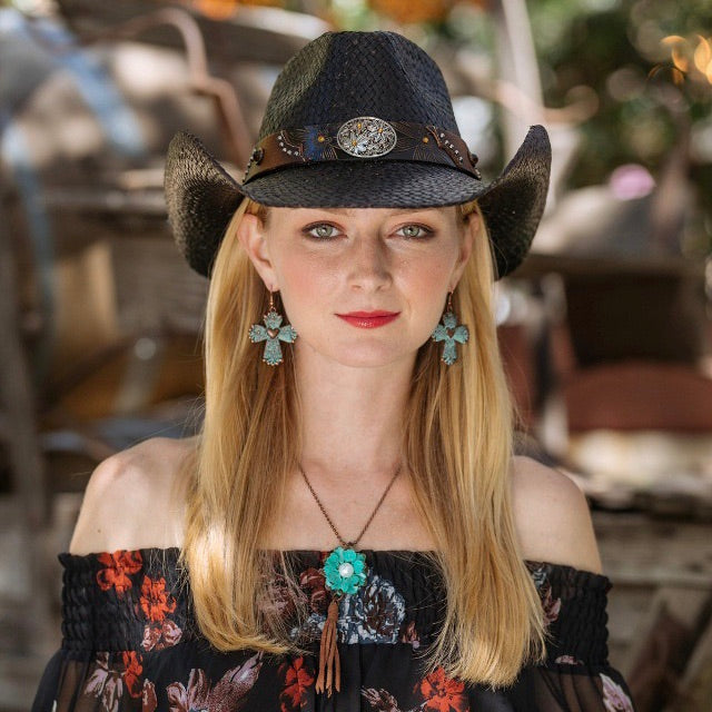 blonde women with black floral crop top and turquoise flower pendant and turquoise cross earrings with black straw cowboy stampede hat and daisy pendant