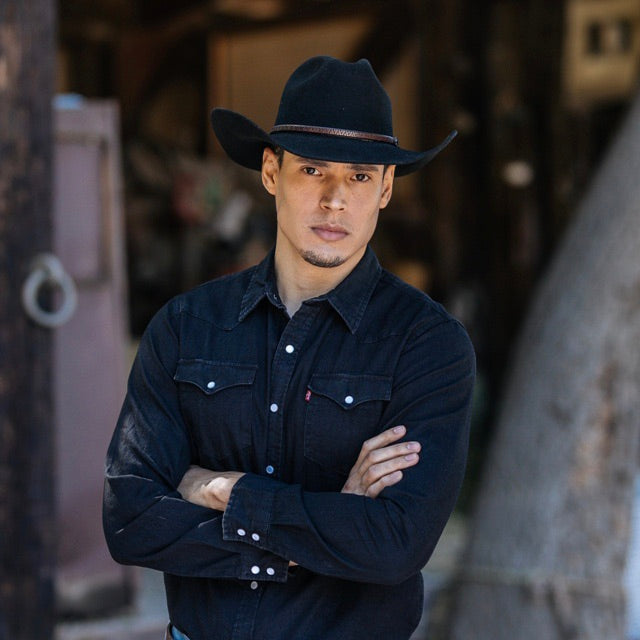 man wearing black button up collared shirt with black wool felt stampede hat with brown leather trim