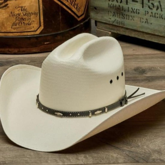 white bangora straw vented cowboy stampede hat with genuine brown leather trim on wooden table