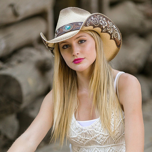 blonde haired women with beige and tank top and tea stained cowboy western stampede hat with turquoise rhinestone and brown and tan floral design
