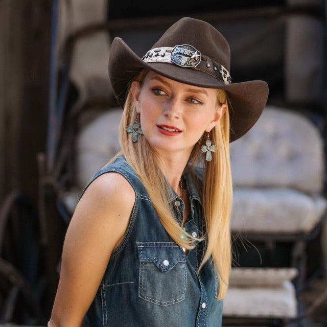 Blonde women wearing denim cut off button up with brown felt stampede cowboy hat with camo style beige belt and cowboy pendant