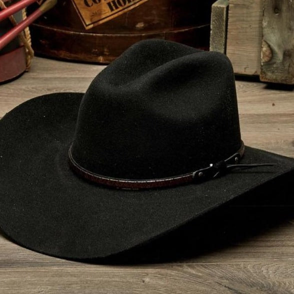 black wool felt stampede hat with brown leather trim on wooden table