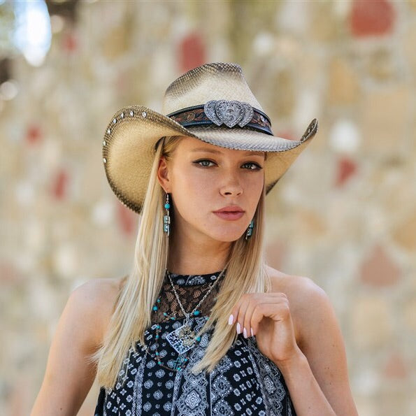 Blonde hair women wearing sleeveless back silky blouse with a stampede cowbow hat on, hat band 3 silver hearts