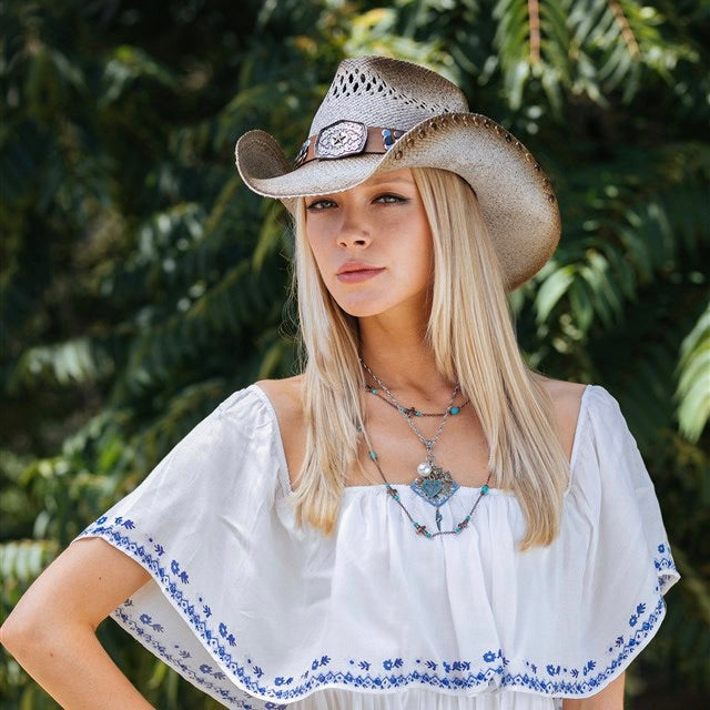 blonde women wearing white cut off dress with a tea stained and brown tinted straw and vented stampede panama womens cowboy hat and a brown band with tacks and large buckle centerpiece with small star in the center