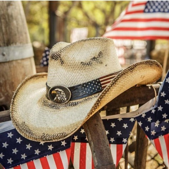panama straw western cowboy stampede hat with american flag band and bald eagle pendant on medal railing with american flags hanging