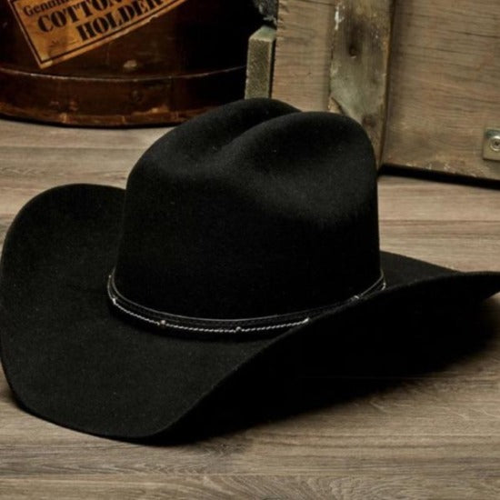 black wool felt stampede western cowboy hat with leather trim on wooden table