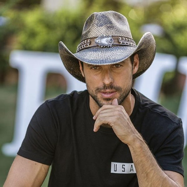 Man in black t-shirt with black hair and facial hair wearing snake skin patterned cowboy western stampede hat and guitar head pendant