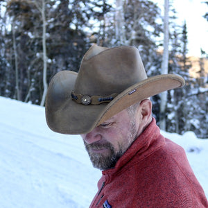 Middle aged man with beard and mustache wearing a red sweater, and stetson leather cowboy hat standing with a snow covered back ground.