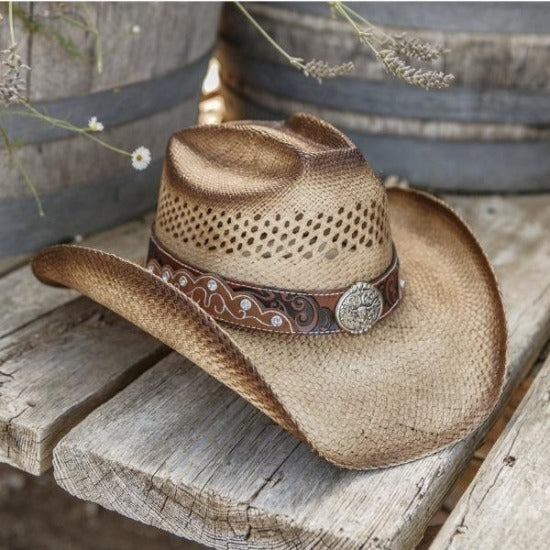 brown straw panama stampede cowboy hat with brown and black band and texas long horn pendant on wooden bench