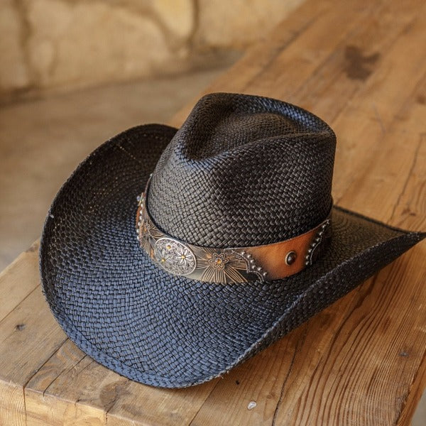 black straw genuine panama womens stampede cowboy hat with brown and black band and silver daisy pendant sitting on brown bench