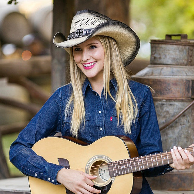 Blonde girl holding a guitar wearing denim shirt and stampede western straw cowboy womens hat with cross pendant