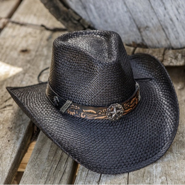 black straw western stampede cowboy hat with black band and star pendant sitting on wooden floor