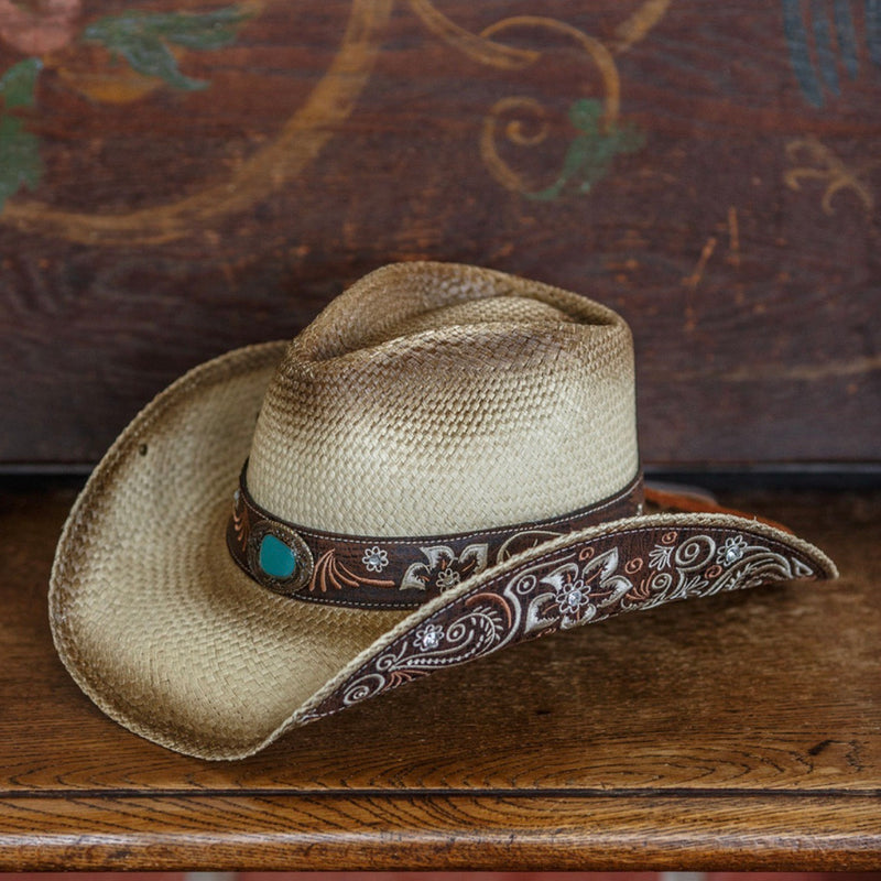 tea stained cowboy western stampede hat with turquoise rhinestone and brown and tan floral design sitting on brown wooden bench