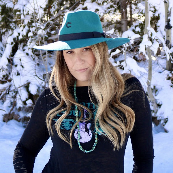 Woman with long blond hair wearing a teal wool charlie 1 horse hat with snow covered pine trees in the back ground.