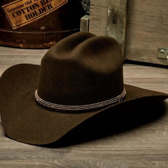 brown wool felt stampede western cowboy hat with leather trim on wooden table