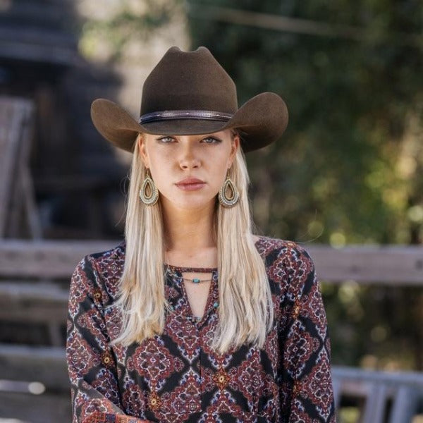 blonde women wearing designed top with brown wool felt stampede western cowboy hat with leather trim