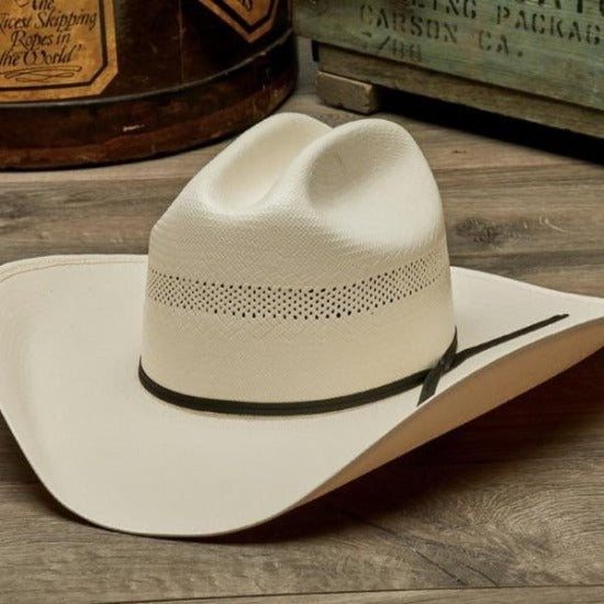 traditional vented western straw stampede hat with black leather trim band wooden table