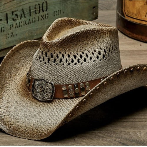 tea stained and brown tinted and vented straw stampede panama womens cowboy hat and a brown band with tacks and large buckle centerpiece with small star in the center on wooden table